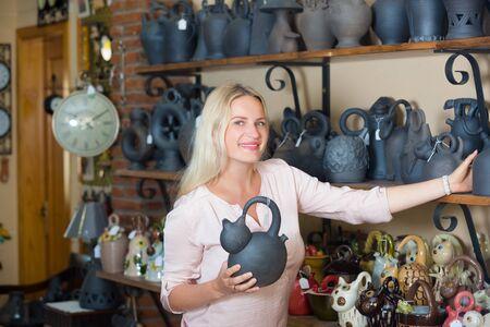 Smilling blonde woman choosing clay or ceramic dish-ware in workshop