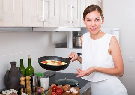 Portrait of smiling young woman cooking egg omelet on kitchen at home