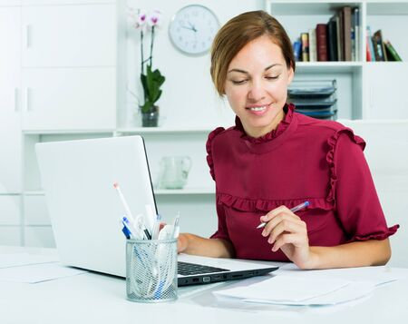 Pretty business woman working at office with laptop and taking notes