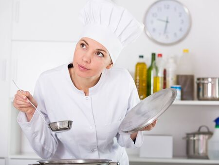 Smiling female cook checking taste of food while preparing in kitchen