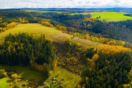 View from drone of natural landscape with autumn mixed woodlands on hillsides