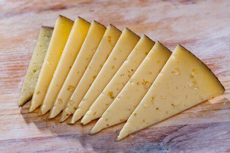 Appetizing slice of semi-hard cheese on wooden surface Zdjęcie Seryjne