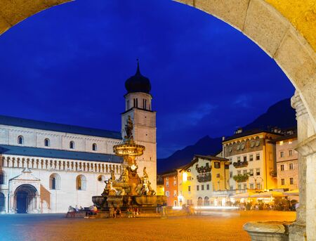 Fountain of Neptune on background of ancient cathedral on Piazza Duomo in Trento in evening, Italy