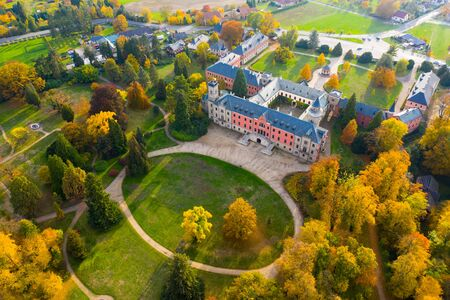 Scenic aerial view of historical neo-gothic Sychrov castle with colorful fall park, Czech Republic