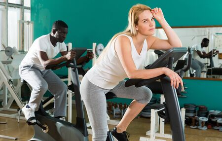 Portrait of tired young woman sitting on exercise bike at sport club