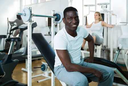 Group of people exercising with weight and on simulators in gym Stock Photo