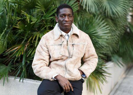 Portrait of cheerful African-American man in warm jacket in urban environment Banco de Imagens