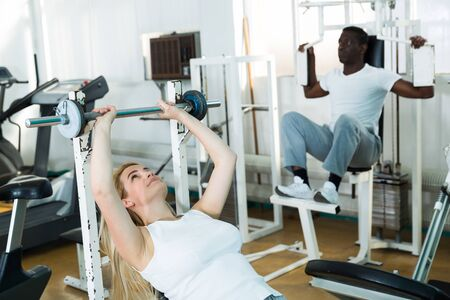 African man and caucasian women exercising on simulators in sport club Stock Photo