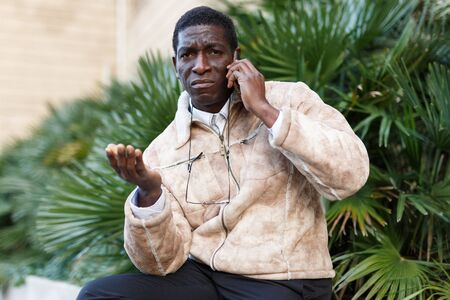 Displeased African man in overcoat talking on smartphone near green plants