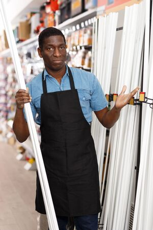Friendly experienced young salesman of household store offering goods