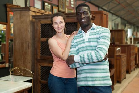 Portrait of happy international couple visiting furnishing store in search of stylish wooden pieces of furniture for home interior Banco de Imagens