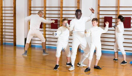 Fencing instructor explaining to young fencers effective movements and techniques at training room  Stock Photo