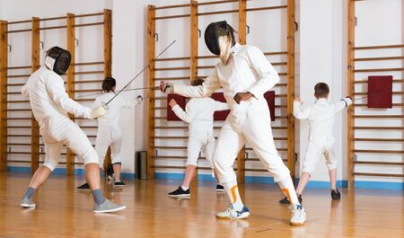 Smiling group  practicing effective fencing techniques in sparring in training room