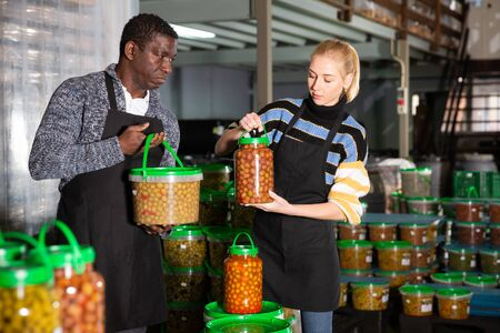 Confident African-American man engaged in producing of pickled olives with young female assistant, stacking plastic packing buckets with finished products