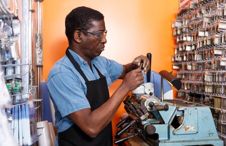 Concentrated locksmith working on key duplicating machine in workshop