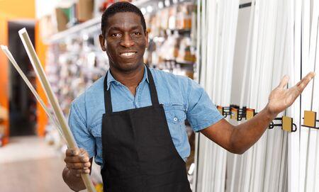 Joyful African American man offering for sale different supplies for renovation works in building hypermarket Banco de Imagens