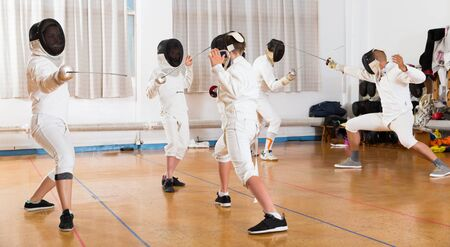 Boys and adults practicing effective fencing techniques in sparring in training room