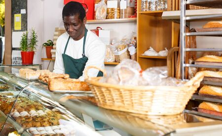 Adult African American baker working in small bakery, arranging showcase with freshly baked bread and pastry