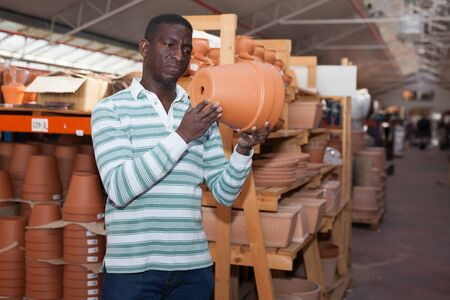 African American amateur gardener looking for flowerpots for growing plants at his smallholding