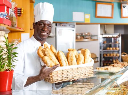 Adult African American bakery chef in white uniform holding wicker basket with freshly baked baguettes at bakeshop