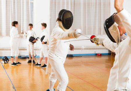 Portrait of kids and adults fencers with coaches engaged in fencing in training room