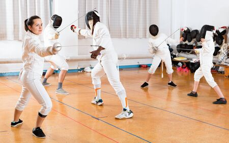 Young cheerful positive woman fencer practicing effective fencing techniques in training room