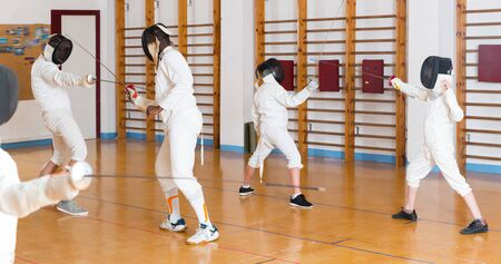 Nice group  practicing effective fencing techniques in sparring in training room Stock Photo