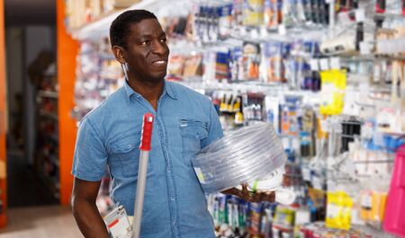 portrait of smiling adult salesman arranging different goods on stand in shop of household materials and tools Banco de Imagens