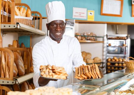 Successful baker wearing white uniform working behind counter in bakeshop, presenting fresh baked products