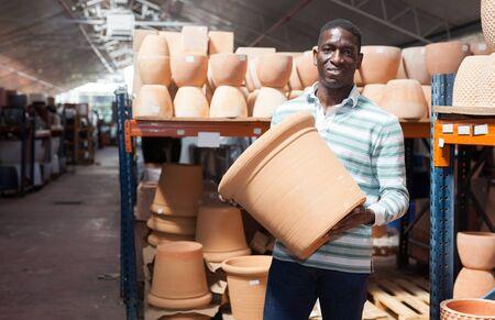 Portrait of African American man choosing pots for flowers and trees in gardening market Banco de Imagens