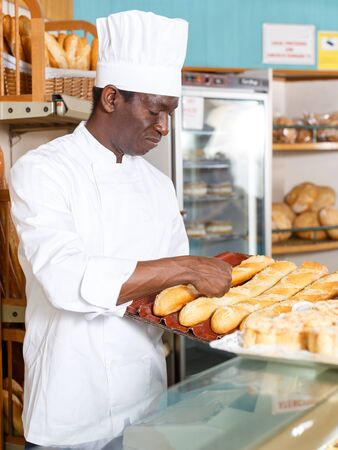 African American worker of bakery preparing fresh baked goods for sale on counter