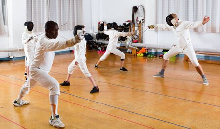 Ijverige positieve coaches demonstreren aan jonge atleten die bewegingen aanvallen met rapier tijdens schermtraining