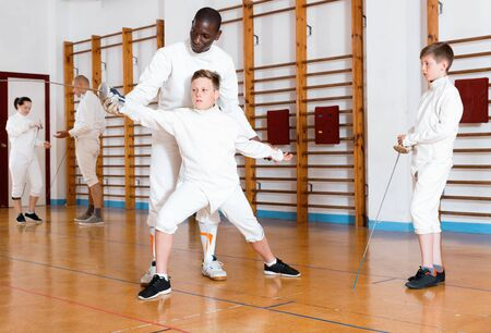 Focused diligent serious positive boys fencers attentively listening to professional  fencing coach in gym Stock Photo
