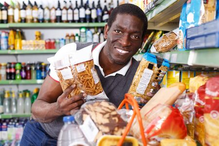 Portrait of positive African man choosing pasta in grocery store