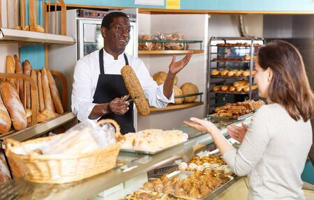 Polite male baker working behind counter in store of his bakery, serving female customer Banco de Imagens