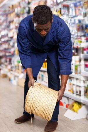 seller of household goods shop organizing assortment of items on shelves and racks Banco de Imagens