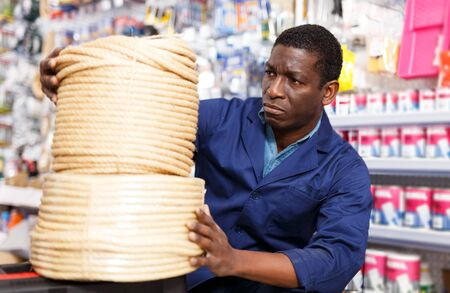portrait of focused salesman arranging different goods on stand in shop of household materials and tools
