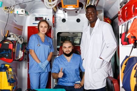 Three positive friendly  smiling efficient ambulance doctors posing in ambulance car with medical equipment