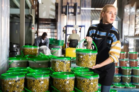 Young woman pickled olives production owner arranging plastic buckets with finished products