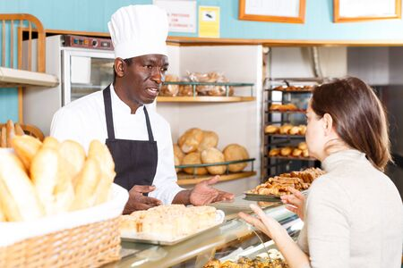 Professional baker standing at counter in bakehouse, selling baked products to female client