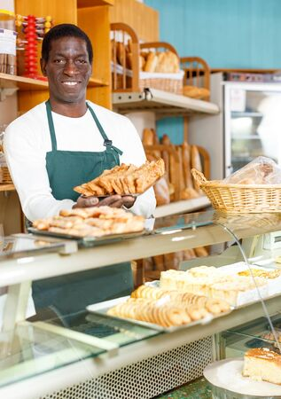 Successful baker working behind counter in bakeshop, presenting fresh baked products