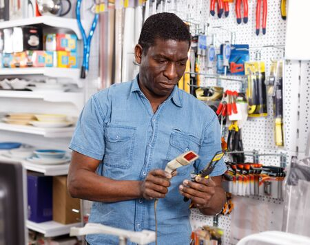 Nice African American salesman working on computer behind counter in store of household goods