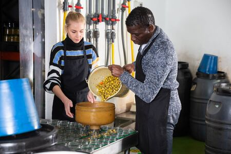 Artisanal producing of pickled olives. Multiracial couple of farmers filling glass jars with marinated olives for canning Banco de Imagens