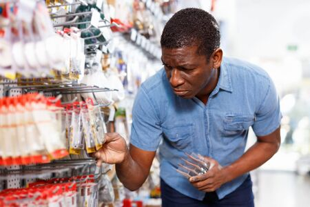 Confident happy  African-American handyman choosing materials for overhauls in household store