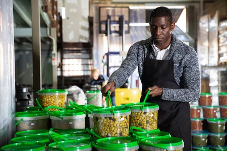 African man worker of pickled olives factory stacking plastic buckets with olives in warehouse