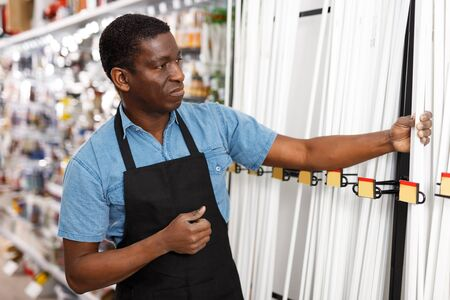 portrait of focused adult salesman arranging different goods on stand in shop of household materials and tools Banco de Imagens