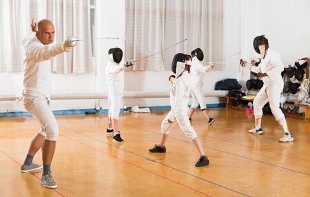 Portrait of sports focused man wearing fencing uniform practicing with foil in gym