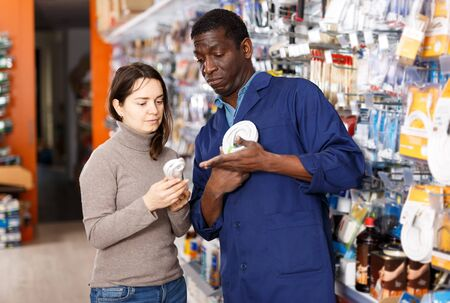 Confident African American man in blue overalls showing different goods to young female client in household shop