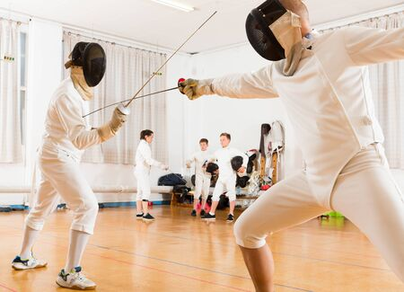 Young fencers looking at fencing duel with foils of two professional trainers in gym