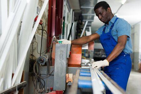 Male master is working with machine in the window workshop. 版權商用圖片